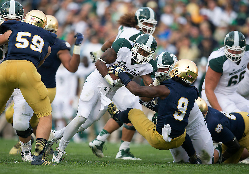 September 21, 2013:  Michigan State running back Jeremy Langford (33) is tackled by Notre Dame linebacker Jaylon Smith (9) during NCAA Football game action between the Notre Dame Fighting Irish and the Michigan State Spartans at Notre Dame Stadium in South Bend, Indiana.  Notre Dame defeated Michigan State 17-13.
