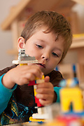 A four-year-old boy playing with Legos