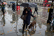 A pet owner and her dog endure heavy rainfall on an autumn afternoon in Trafalgar Square, on 24th October 2019, in Westminster, London, England.