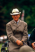 The Prince Philip, Duke of Edinburgh (born Prince Philippos of Greece and Denmark; born 10 June 1921) is seen driving a carriage at the Lowther Show in Cumbria. Enjoying his favourite pastime of carriage racing he looks relaxed and happy to be able to enjoy this sport of the socially privileged. Holding the reins and about to put another glove on his hand, the Duke is dressed in tweed and wears a tie and hat that has a horse badge on the front. The Duke was also a Polo player in his youth and adult life; though he eventually gave up the sport due to age but carried on competing in carriage driving, a sport which he helped expand, and for which he wrote the early rule book