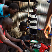 """Burundian university students, seeking shelter outside the US embassy in Bujumbura, serve lunch in the yard of a vacant building close by. The students moved to the area in early May because, they claim, the US authorities ensure their security, after their university was closed amid anti-government protests. The government closed the university at the end of April, citing """"insecurity""""."""