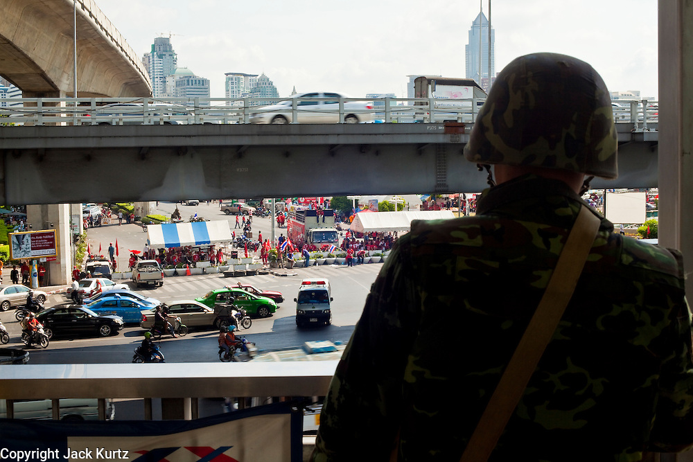 Apr. 19 2010 - BANGKOK, THAILAND: A Thai soldier on an elevated walkway watches the Sala Daeng intersection at the entrance to the Silom financial district Monday. Hundreds of Thai soldiers, including reservists and front line units, and riot police moved into the Silom financial district Monday, not far from the red-shirts' main protest rally site, in Ratchaprasong. The heavy show of force is to prevent the Red Shirts from entering the Silom area. Many of soldiers were greeted as heros by workers in the area, who oppose the Red Shirts.   Photo by Jack Kurtz