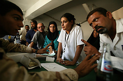 U.S. soldier Juan Arevalo, 20, is lectured by an angry Iraqi as translator Alyaa Abdul Hassan Abbood, center, 23, as she mediates the interaction, Baghdad, Iraq, Sept. 27, 2003. Iraqi civilians crowded into the courtroom to receive monetary compensation for damages done by American troops in Baghdad.
