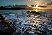 The surf surges on the rocks of Sharks Cove as the sun sets over Kaena Point on Oahu's north shore, Hawaii