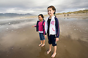 Best friends Vira Halim-Rotinsulu (left) and Isabel Durham, both nine years old, face the surf at the Oregon Coast. (Fully released - 111106)
