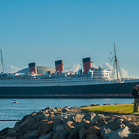 Tourists admire the Queen Mary cruise ship, now a floating hotel in Long Beach, California.