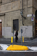 Woman passes road island in Florence's Via de Bardi on south bank of city, near Ponte Vecchio.
