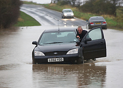 © Licensed to London News Pictures. 25/11/2012..North East England..A man working for a recovery service pushes a stranded car that became stuck in deep water near to Staithes in North Yorkshire this morning following heavy overnight rain that caused traffic disruption and flooding in parts of Cleveland and North Yorkshire...Photo credit : Ian Forsyth/LNP