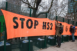 London, UK. 31 January, 2021. Anti-HS2 activists from umbrella campaign group HS2 Rebellion hang a 'Stop HS2 Now - Battle for Euston' banner from fencing erected by HS2 Ltd around Euston Square Gardens. Climbers from the National Eviction Team (NET) are currently dismantling a camp built by activists, five of whom still occupying tunnels beneath the camp, in order to seek to protect trees from felling by HS2 Ltd in connection with the controversial HS2 high-speed rail project.