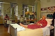 With fresh flowers on her bedside table and get-well cards from well-wishers, an elderly lady patient lies on her hospital bed during her recovery at the Royal London Homoeopathic Hospital, the leading centre for complementary medicine at 60 Great Ormond Street, central London. The Royal London Homoeopathic Hospital provides complementary medicine treatment to outpatient and inpatients from virtually anywhere in the UK: From allergy & nutritional medicine; a children's clinic; complementary cancer care; podiatry & chiropody; musculoskeletal medicine; pharmacy services; rheumatology; skin services; stress & mood disorders and here, a women's clinic. There are other female patients also lying in bed, chatting or knitting.