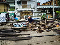 August 16, 2017 - Bangkok, Bangkok, Thailand - A home scavenges used construction wood left behind after city officials tore down several homes built on pilings in the Wat Thewarat Kunchorn community along the Chao Phraya River in Bangkok. City officials are evicting people who live in small homes along the riverfront so they can build a 14km long promenade. Their plans call for removal of 273 homes in 14 riverside communities. The people who live in the homes are among the most impoverished in Bangkok. (Credit Image: © Sean Edison via ZUMA Wire)