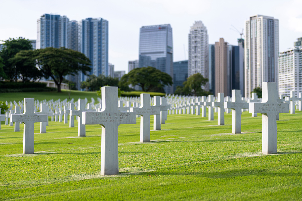 The grave of Charles R. Chastain and some 17,000 others, most of whom lost their lives in WWII, at the Manila American Cemetery in Manila, Philippines. In the background are the highrises of Bonifacio Global City, a modern district of Manila.