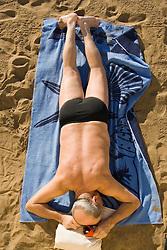 Man sunbathing on the beach in the Canary Islands