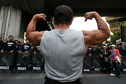 © Licensed to London News Pictures. 26/05/2014. An anti-coup protestor flexes in muscle in protest in front of a line of riot police during a Anti-Coup protest in Bangkok Thailand. Today Thailand's King formally approved Thai army chief General Prayut Chan-O-Cha as head of the nation's new military junta.  Photo credit : Asanka Brendon Ratnayake/LNP