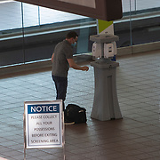 A passenger at Orlando International Airport fills his bottle with hand sanitizer before boarding the train to his gate on Friday, April 17, 2020 in Orlando, Florida. (Alex Menendez via AP)