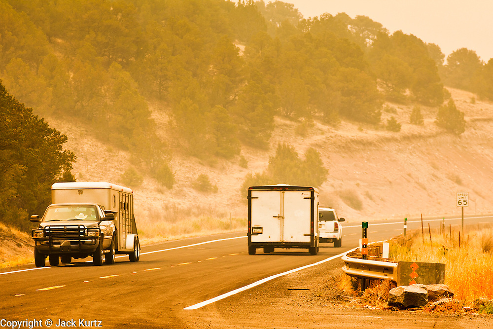 """03 JUNE 2011 - SPRINGERVILLE, AZ: Smoke shrouded traffic on US Highway 180 north of Alpine and Nutrioso. The road is closed from Nelson Reservoir to south of Hannigan's Meadow. High winds and temperatures have continued to complicate firefighters' efforts to get the Wallow fire under control. The  mandatory evacuation order for Alpine was extended to Nutrioso, about 10 miles north of Alpine and early Friday morning fire was reported on the south side of Nutrioso. The fire grew to more than 106,000 acres early Friday with zero containment. A """"Type I"""" incident command team has been called in to manage the fire.  PHOTO BY JACK KURTZ"""