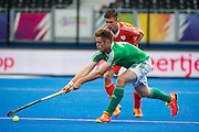Ireland's Shane O'Donoghue is watched by Thierry Brinkman of The Netherlands. Ireland v The Netherlands - Semi-Final Unibet EuroHockey Championships, Lee Valley Hockey & Tennis Centre, London, UK on 27 August 2015. Photo: Simon Parker