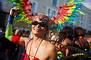 A woman dressed up in feathers enjoys the sun and taking part in the carnival.The Notting Hill Carnival has been running since 1966 and is every year attended by up to a million people. The carnival is a mix of amazing dance parades and street parties with a distinct Caribbean feel.