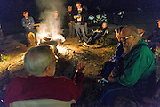 Variou motorcyclists gather around the campfire at The Hub motorcycle resort in Marble Falls, AR after a fun day of riding.