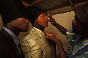 Two young Xhosa male initiates, who have just returned home as men after one month of seclusion, are having their faces painted red by their guardian and teacher in Khayalethu South Township, Knysna, South Africa, in December, 2006. As initiates they were first circumcised, and they then spent one month in a special initiation camp, away from the normal living areas. For one week they will now wear red facial paint, a turban, long trousers, a shirt and a jacket, all signs that they have become men. When the week is over, the turban will be changed for a cap, which will then be worn for another six months.