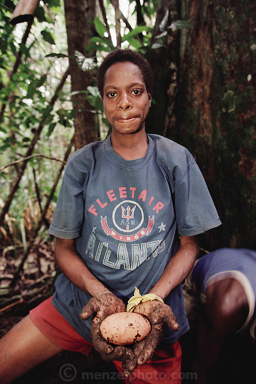 A woman from Sawa Village on the Pomats River in the Asmat, a large, steamy hot tidal swamp, shows a jungle chicken egg which she has just dug up from a 6 foot mound where the bird has made a nest that looks like a compost hump. Irian Jaya, Indonesia. Image from the book project Man Eating Bugs: The Art and Science of Eating Insects.