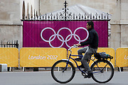 A cyclist pedals past the IOC's Olympic logo brand of rings on a banner at Horse Guards in Whitehall during the London 2012 Olympics. Wrought iron railings are seen behind the banner at the sports venue hosting the volleyball in the centre of Westminster where governmental offices are located.