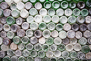 Color film photograph of a wall of neatly stacked multi-colroed glass bottles in Dai Bai bronze casting craft village, Bac Ninh Province, Hanoi outskirts, Vietnam, Southeast Asia