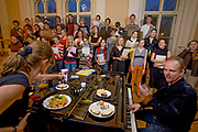 Ansis Souka, 45, VOICE TEACHER, rehearses with the Kamer Latvian youth choir in Riga, Latvia. On the piano is one day's food of Ansis Souka. What I Eat: Around the World in 80 Diets. MODEL RELEASED.'