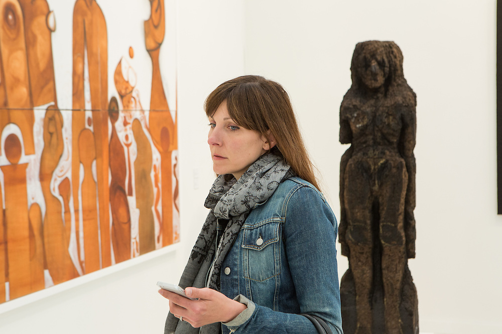 """New York, NY - 6 May 2016. Frieze New York art fair. A woman in the gallery of Salon 94 of New York. On her left is the painting """"Flamenco Dancers"""" by Ibrahim El-Salahi; behind her a sculpture in cork by Huma Bhabha, titled """"Scout."""" by"""