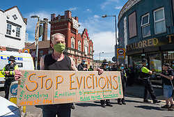 """© Licensed to London News Pictures; 04/06/2021; Bristol, UK. A man holds a placard saying """"Stop Evictions"""" as police mount a major operation to enter the former Salvation Army building behind him on Dean Lane in Bedminster which has been squatted and arrested 3 people suspected of criminal activity connected with the squatted occupation of buildings in High Street in Bristol city centre which was repossessed earlier this morning by Bailiffs accompanied by around 100 police, but those occupying the buildings in High Street had already left. Those arrested at the Salvation Army building are a 40-year-old man on suspicion of assaulting an emergency worker and escaping lawful custody, a 26-year-old man on suspicion of assaulting an emergency worker and escaping lawful custody, and a woman on suspicion of affray. Police were not evicting the Salvation Army building on Dean Lane as they do not have powers to do so. Photo credit: Simon Chapman/LNP."""