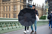 A man smiles as he struggles with an umbrella during heavy rain fall and windy weather on Westminster Bridge in London, United Kingdom on 16th August 2019.