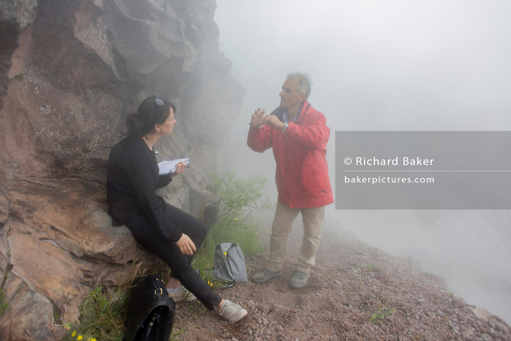 On the crater edge of the Vesuvius volcano, Italy, writer Polly Morland interviews volcanologist with the Osservatorio Vesuviano, Giuseppe Mastrolorenzo for the chapter entitled 'Under the Volcano' and from the book 'Risk Wise: Nine Everyday Adventures' by Polly Morland (Allianz, The School of Life, Profile Books, 2014).