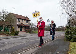 © Licensed to London News Pictures; 04/03/2021; Thornbury, South Gloucestershire, UK. JANE SMITH (left) does her 'March for Mum' daily exercise walk around her area with friend LYNFA FISHER (right) carrying placards campaigning to unlock care homes to allow greater visiting access. Jane's mother Rita is 94, has dementia and is in Windmill House care home nearby. Rita also has an abdominal aneurysm and Jane fears she could die at any time and believes Rita's condition has deteriorated in the last year partly due to lack of contact with family visits. Before covid Jane used to visit Rita every day for several hours, but in the last year has only been able to visit her a few times due to restrictions on visits during the covid coronavirus pandemic. Jane last visited on 11 January when she had to stand outside in the snow and look through the window, but her mother slept the whole time and so Jane had no communication with her. The care home had cases of covid a month ago and with visits to the home now banned Jane will not be able to see her mother when care homes open up on 08 March or on Mothers' Day. Some care homes interpret public health guidelines differently from others, and Jane is campaigning with Care Unlock to lobby for greater safe access for families to visit relatives in care homes. Photo credit: Simon Chapman/LNP.