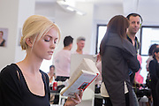 A model reads backstage as she waits for the Carmen Marc Valvo Spring 2013 show at Fashion Week in New York.