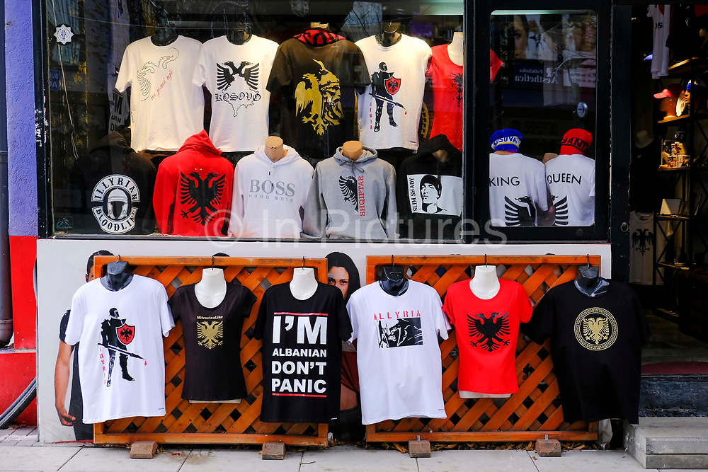 An Albanian t-shirt shop in the south side of Mitrovica, a town in Northern Kosovo that straddles the river Ibar which separates the Serbian and Albanian districts of Mitrovica, Kosovo on the 12th of December 2018.  Mitrovica or Kosovska Mitrovica is a city and municipality located in Kosovo. Settled on the banks of Ibar and Sitnica rivers, the city is the administrative center of the Mitrovica District.