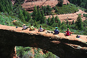 Global Fitness Adventures Health Spa clients meditate on a sandstone arch, Sedona, Arizona..