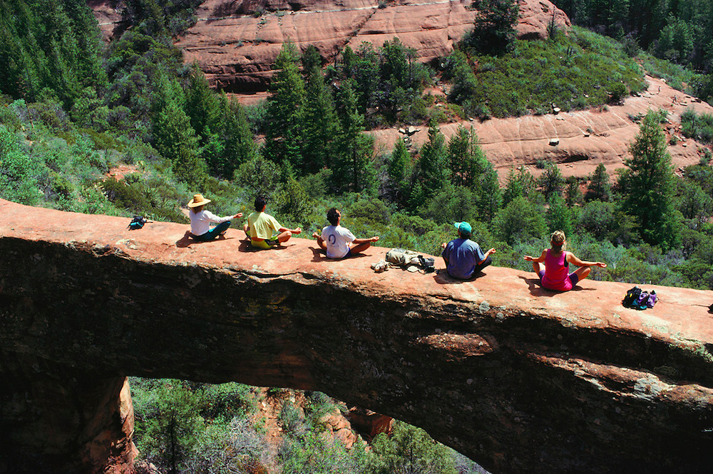 Global Fitness Adventures Health Spa clients meditate on a sandstone arch, Sedona, Arizona..