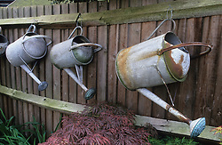 Watering cans displayed on fence. Design: Virginia Pizzaferio
