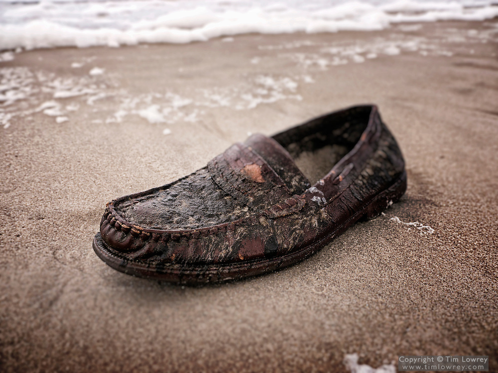 A disgarded shoe is washed up on a beach.