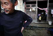 A young boy stands by a door while his grandfather peeks out the courtyard in the village of Duntang, in Daoxian County, Hunan Province, China, on 03 June, 2010. Duntang was connected to the main electricity grid and began to receive regular supply of electricity only since the beginning of 2009.