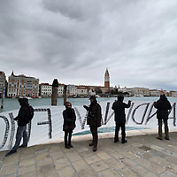 VENICE, ITALY - DECEMBER 18:  Protesters on the Grand Canal hold  a banner as they protest against large cruise ships in St Mark's basin on December 18, 2011 in Venice, Italy. Venetians and Environmentalists are opposed to cruise ships, which plough through the shallow Venetian lagoon, damaging the fragile buildings and canal banks.