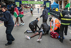 NYRR New York City Half Marathon: Mo Farah on ground after collapse after finish of race, receives medical attention as Mary Wittenberg, race director, attends