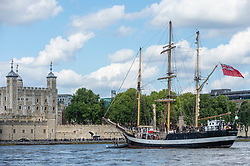 """© Licensed to London News Pictures. 10/08/2021. LONDON, UK.  The tall ship """"Pelican of London"""" next to the Tower of London.  Unique among Square Riggers, her hull form was derived from the elite French clippers of the late 19th century, with a length to breadth ratio of 5:1.  She will be moored next to HMS Belfast until 14 August.  TS Pelican is designed principally as a sail training ship but also competes in events worldwide.  Photo credit: Stephen Chung/LNP"""