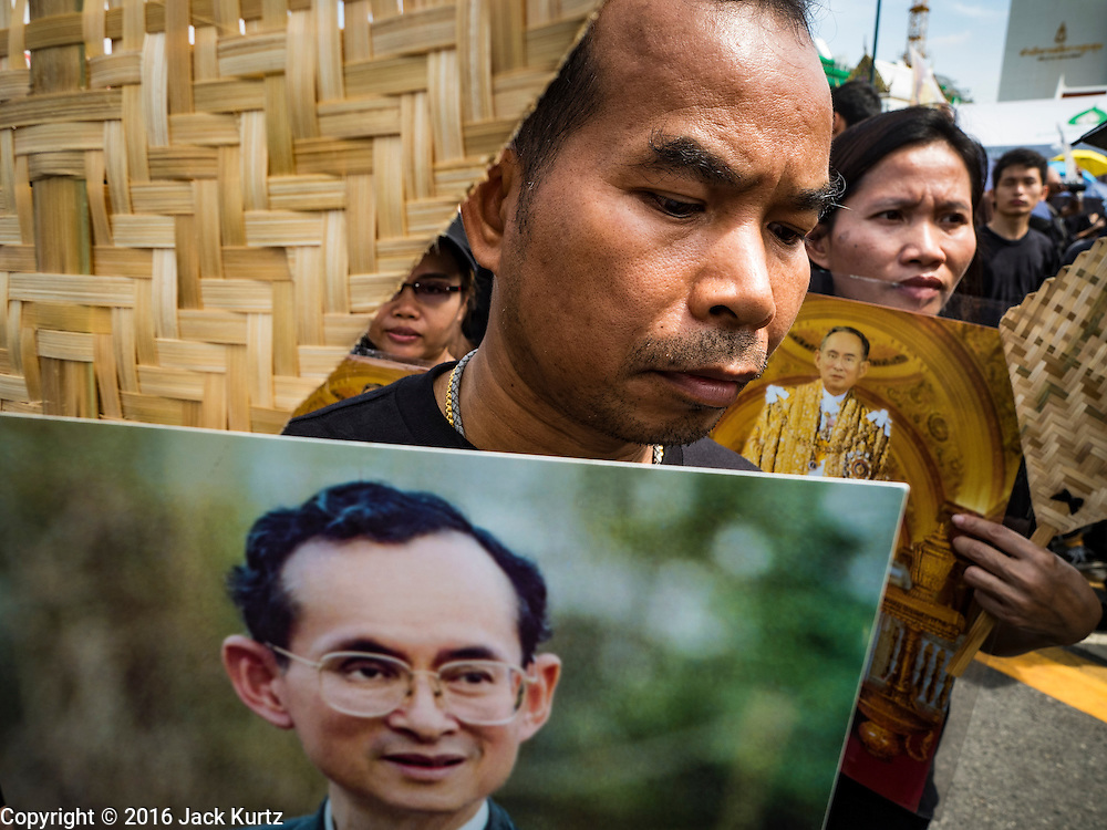22 OCTOBER 2016 - BANGKOK, THAILAND: Mourners hold portraits of the late Bhumibol Adulyadej, the King of Thailand, during the singing of the King's Anthem on Sanam Luang Saturday. Sanam Luang, the Royal Ceremonial Ground, was packed Saturday with more than 100,000 people mourning the Monarch's death. The King died Oct. 13, 2016. He was 88. His death came after a period of failing health. Bhumibol Adulyadej was born in Cambridge, MA, on 5 December 1927. He was the ninth monarch of Thailand from the Chakri Dynasty and is also known as Rama IX. He became King on June 9, 1946 and served as King of Thailand for 70 years, 126 days. He was, at the time of his death, the world's longest-serving head of state and the longest-reigning monarch in Thai history.       PHOTO BY JACK KURTZ
