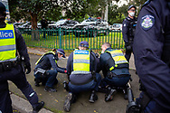A woman is pinned to the ground by 4 officers for standing in support of the residents inside of 120 Racecourse road amid the third full day of the total lockdown of 9 housing commission high rise towers in North Melbourne and Flemington during COVID 19.After recording 191 COVID-19 cases overnight forcing Premier Daniel Andrews to announce today that all of metropolitan Melbourne along with one regional centre, Mitchell Shire will once more go back to stage three lockdowns from midnight Wednesday June 8. This comes as the residents of the housing commission towers in North Melbourne and Flemington finish their third day under extreme lockdown, despite only 27 cases being found in the towers. Members of the public gathered outside of the towers this afternoon in support of those trapped inside while riot police arrested two women for standing too close to the fence. While the women were later released, tensions are boiling over both in the towers and out. With 772 active cases in Victoria, NSW closed their border to Victoria effective at midnight tonight.