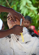 Head shaving at Thaipusam Festival, Batu Caves, Malaysia. Many pilgrims prepare for the day by cleansing, fasting and abstinence before having their head shaved. Thaipusam is a Hindu festival celebrated mostly by the Tamil community on the full moon in the Tamil month of Thai (Jan/Feb). The festival celebrates the birth of Murugan,the youngest son of Shiva and his wife Parvati. The festival at Batu Caves, Kuala Lumpur culminates in a 272 step climb into the cave.