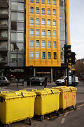 Colourful street scene with yellow commercial bins near to the Google offices in London, United Kingdom.