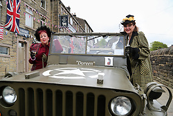 © Licensed to London News Pictures. 13/05/2016. Haworth, UK. Two woman in 1940s costume enjoy glasses of wine inside a military jeep during the annual 1940's weekend in Haworth, West Yorkshire.  Photo credit : Ian Hinchliffe/LNP