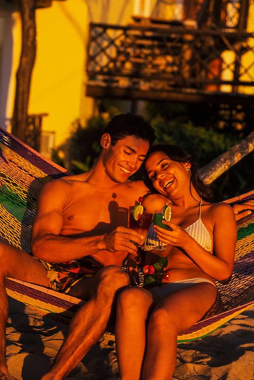 Couple having cocktails on the beach, Reef Club Beach Resort, Isla Cozumel, Mexico