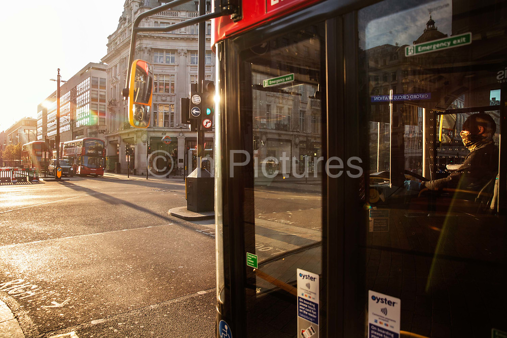 Bus driver wearing a protective mask in a deserted Oxford Circus at rush hour during the Coronavirus pandemic on 26th March 2020 in London, United Kingdom. The public were not allowed to leave their homes except for a few specific reasons, and could be fined £30 for meeting outside in groups of more than two people.